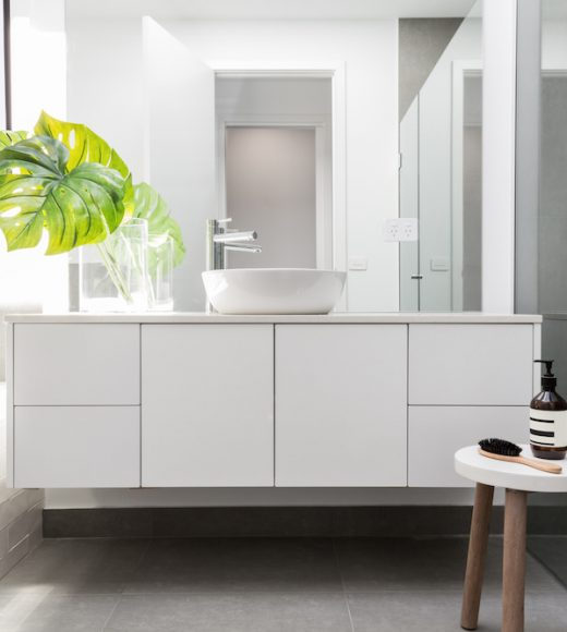 Luxury white family bathroom styled with greenery and a wooden stool